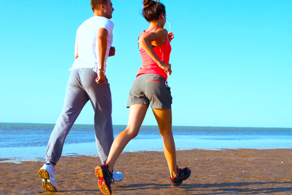 Young couple running together beside the water at the beach. Man and woman training outdoors.