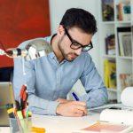 man-writing-on-a-desk_1301-48